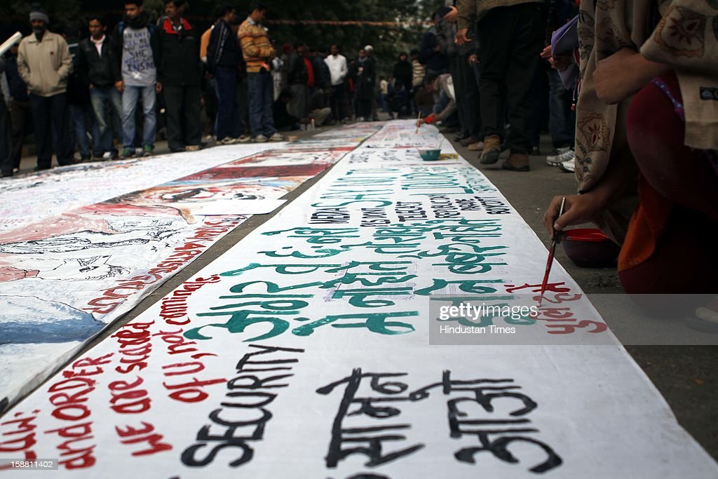 People show their anger and support through series of paintings and slogans on large canvas during protest at Jantar Mantar for girl who died of injuries after brutally gang raped in a moving bus on December 30, 2012 in New Delhi, India. The young woman was cremated promptly on Sunday amid an outpouring of anger and grief by millions across the country demanding greater protection for women from sexual violence.