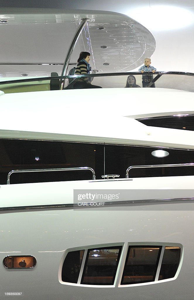 People show their toddler around a luxury motor boat on display at the 2013 London Boat Show in east London on January 12, 2013. The nine-day show features everything from speedboats to dinghies, boat paint to hot tubs with exhibits from many major marine and watersports related brands.