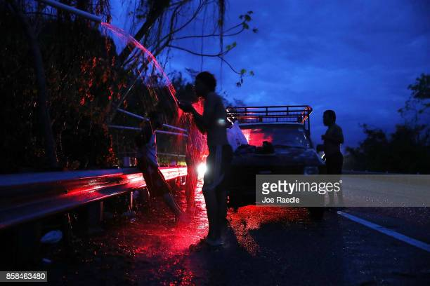 People shower in spring water flowing from a pipe along side a highway since they have no running water in their home after Hurricane Maria passed...
