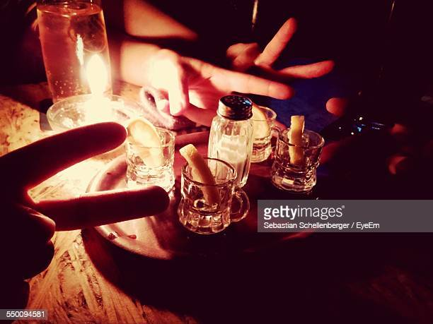 People Showing Peace Sign At Illuminated Table With Tequila Shot