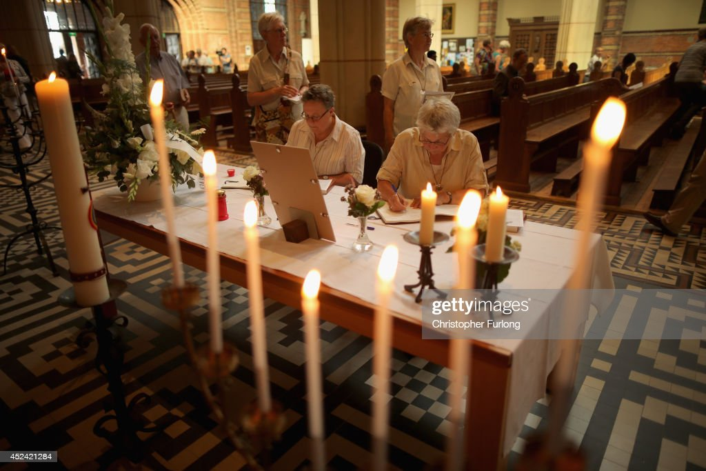 People sign a book of condolence during a special mass in Saint Vitus church in memory of the victims of Malaysia Airlines flight MH17 on July 20...