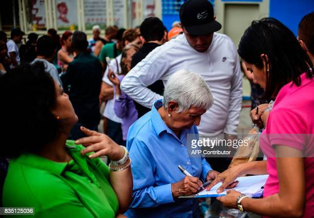 People sign a list after getting their foodstuff bag at one of the food distribution centers called CLAP which are run by community leaders in a...
