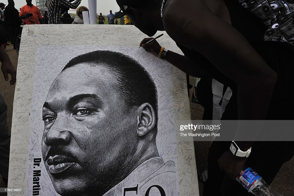 People sign a poster with Martin Luther King Jr's face as they make their way to the march at the mall. Citizens from across the country rally to commemorate and celebrate the historic March On Washington which occurred 50 years ago today August 28, 1963.
