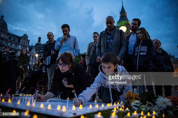 People sign messages of condolence for MP Jo Cox during a vigil in Parliament Square on June 16 2016 in London United Kingdom Jo Cox Labour MP for...