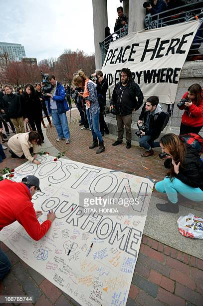 People sign messages on a banner during a vigil on the Boston Common April 16 2013 in Boston Massachusetts in the aftermath of two explosions that...