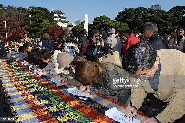 People sign their names in congratulatory books December 2 2001 outside the Imperial Palace in Tokyo Japan one day after Crown Princess Masako gave...