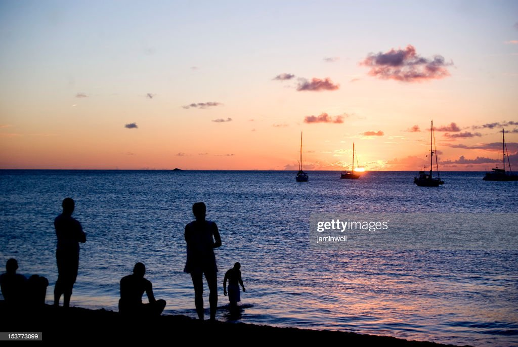 people silhoettes on colorful beach at sunset balanced by yachts : Stock Photo