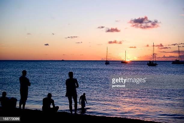 Menschen silhoettes auf bunten Strand bei Sonnenuntergang durch Yachten