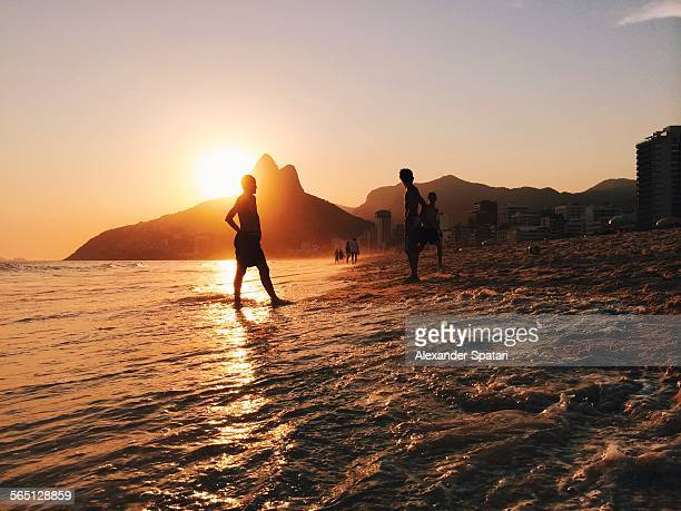 People silhouettes on Ipanema beach in Rio, Brazil