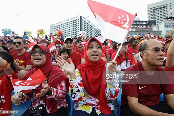 People sing along during the preparade segment during the National Day Parade at the Float at Marina Bay on August 9 2014 in Singapore Singapore...