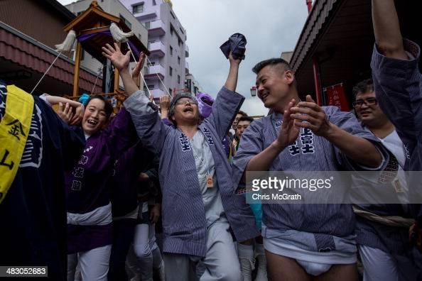 People sing and dance as they carry a large black phallicshaped 'Mikoshi' through the streets during Kanamara Matsuri on April 6 2014 in Kawasaki...