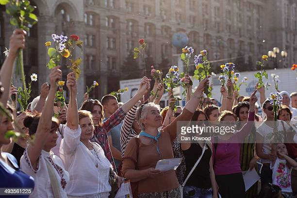 People sing and wave flowers as a 'flash mob' perform traditional Ukrainian songs and pray for a peaceful election in Maidan Square on May 24 2014 in...