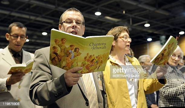 People sing as they attend the annual Jehovah's Witnesses assembly gathering 30000 believers on July 22 2011 in Villepinte Paris suburb European...