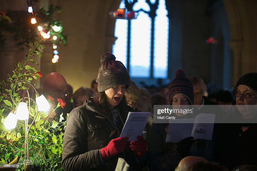 People sing Christmas carols at the fifth annual carol service being held inside the 13th century St Giles church in the village of Imber on December...