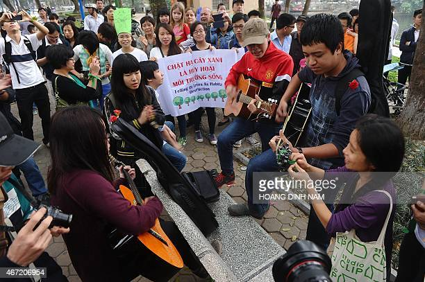 People sing during a rally protesting against a treefelling plan by the municipal authorities in Hanoi on March 22 2015 Vietnam abandoned plans to...