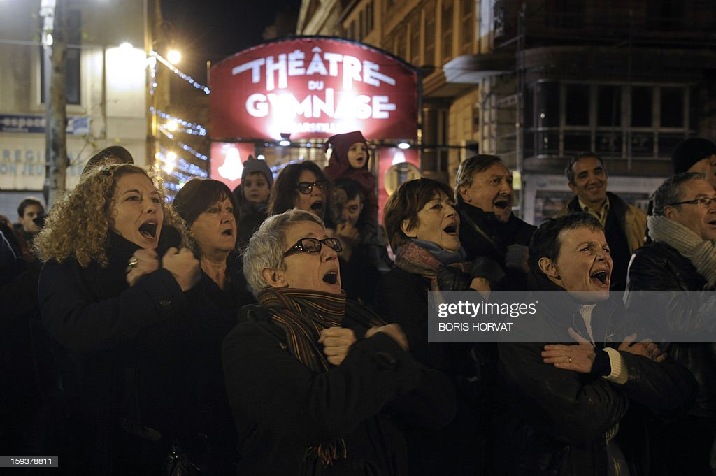 People sing in front of the Theatre du Gymnase, on January 12, 2013 at the Vieux-Port harbour in Marseille, southern France, as part of the opening festivities marking Marseille as the 2013 European Capital of Culture. AFP PHOTO / BORIS HORVAT