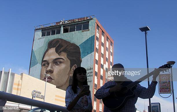 People sing next to a building with a mural depicting the face of Mexican singer Juan Gabriel in Ciudad Juarez on August 28 2016 Mexican singer...