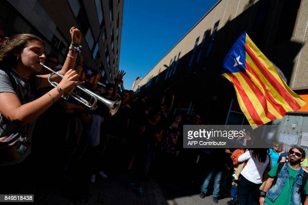People sing the Catalan anthem and hold an 'Estelada' in protest against a search for propaganda supporting Catalonia's independence referendum by...