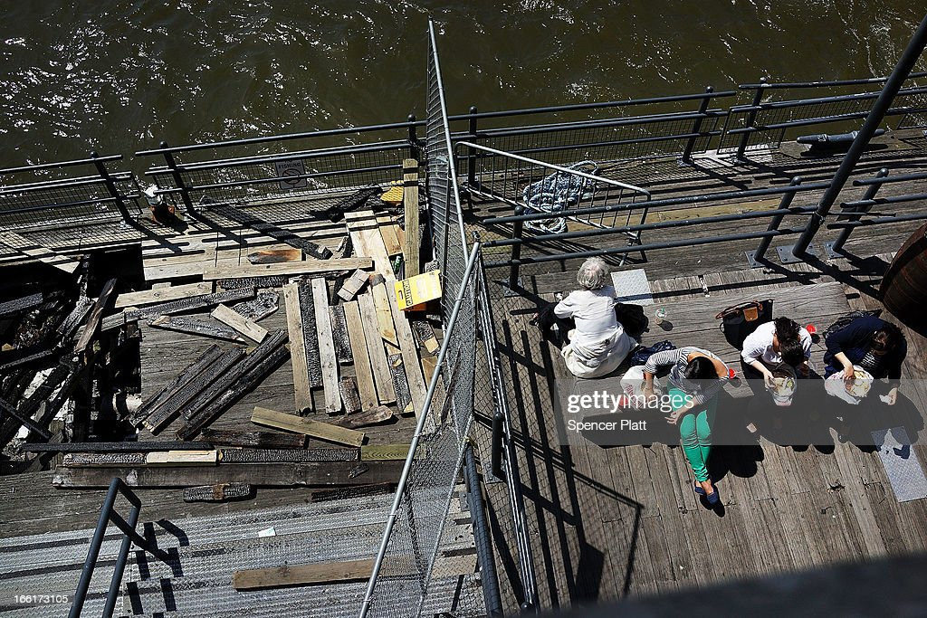 People sit along the East River at South Street Seaport near a damaged section of dock from Hurricane Sandy on April 9, 2013 in New York City. For the first time since October, temperatures are expected to rise above 70 degrees this week in New York and surrounding areas.