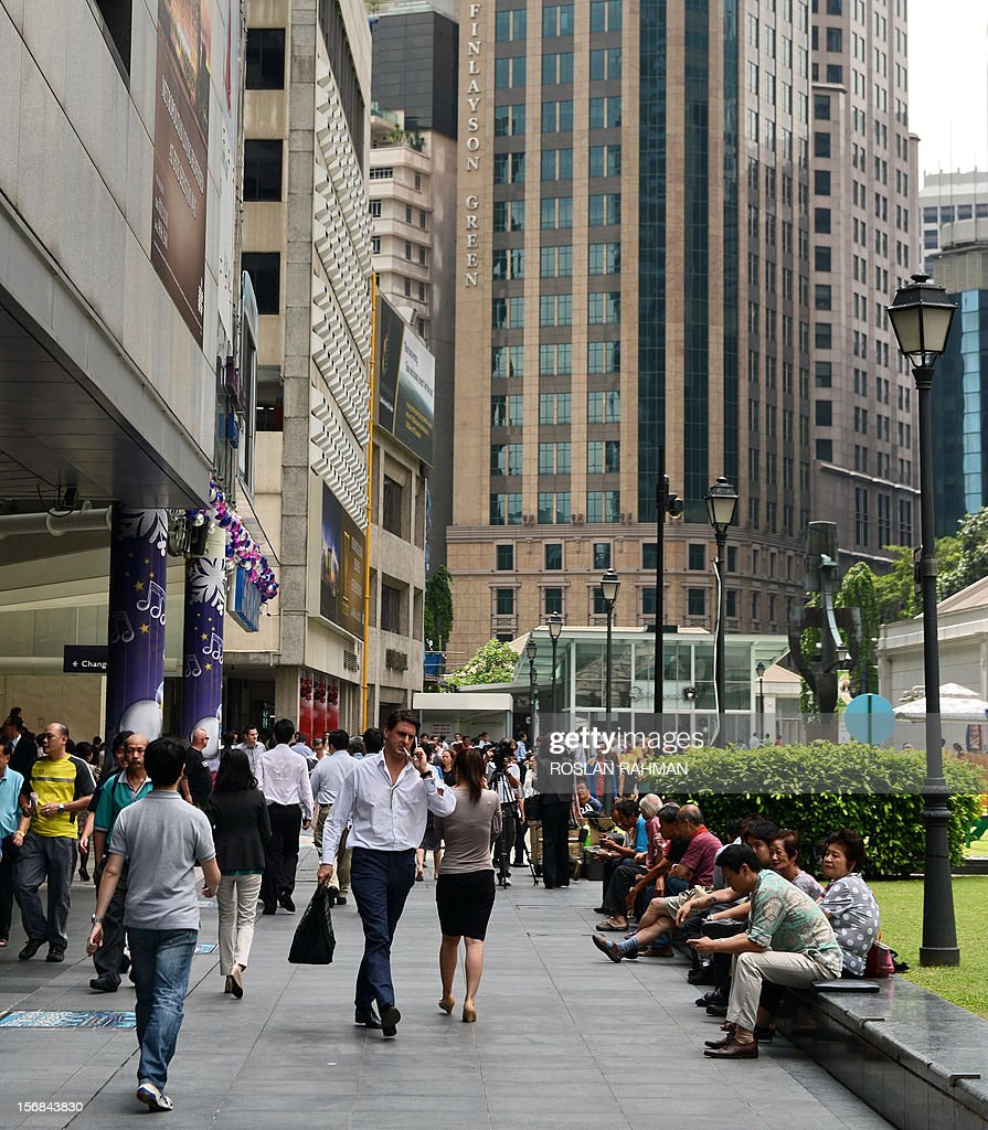 People sit along the promenade in the financial district during their lunch break in Singapore on November 23, 2012. Singaporeans have rejected a survey depicting them as the world's most emotionless people, with many saying they are in touch with their feelings, albeit overwhelmingly negative ones.