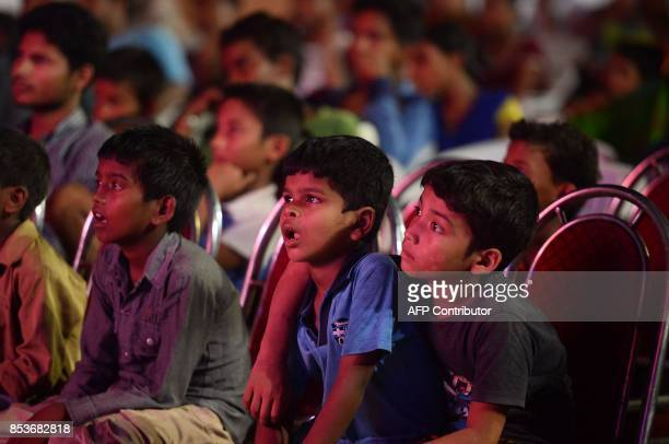 People sit along the road side watching an Indian epic television series of Ramayana the story of the battle of Hindu god Rama over the demon king...