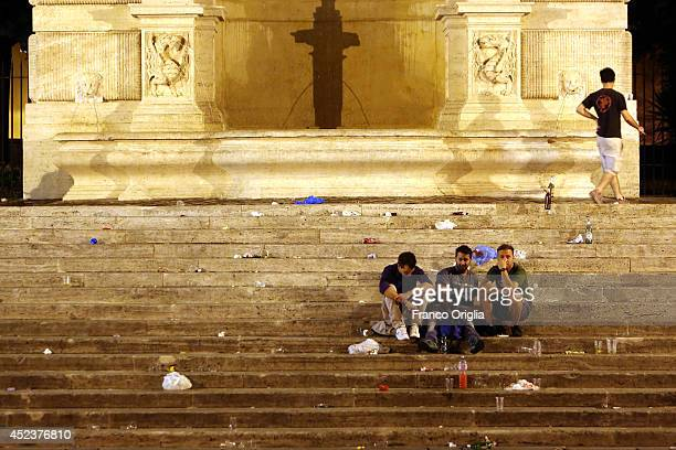 People sit amongst garbage at Piazza Trilussa in Trastevere Rome's historical district after a Roman Friday night out on July 15 2014 in Rome Italy...
