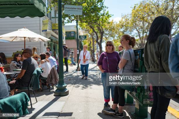 People sit and eat at outside tables at Chocolatier Blue while others wait for tables on the sidewalk in the Fourth Street shopping district Berkeley...