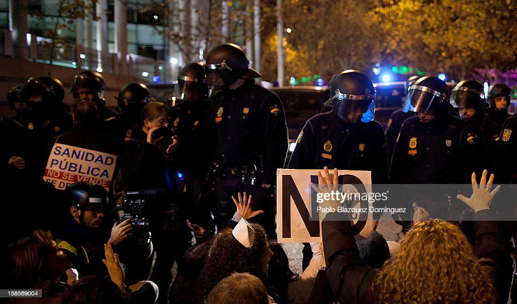People sit and shout slogans in front the riot police line during a health care workers demonstration outside Madrid Regional Asembly on December 19, 2012 in Madrid, Spain. As of today, health workers unions are calling for a third 48-hour strike against cuts on public health care and the privatization of medical centers and hospitals.