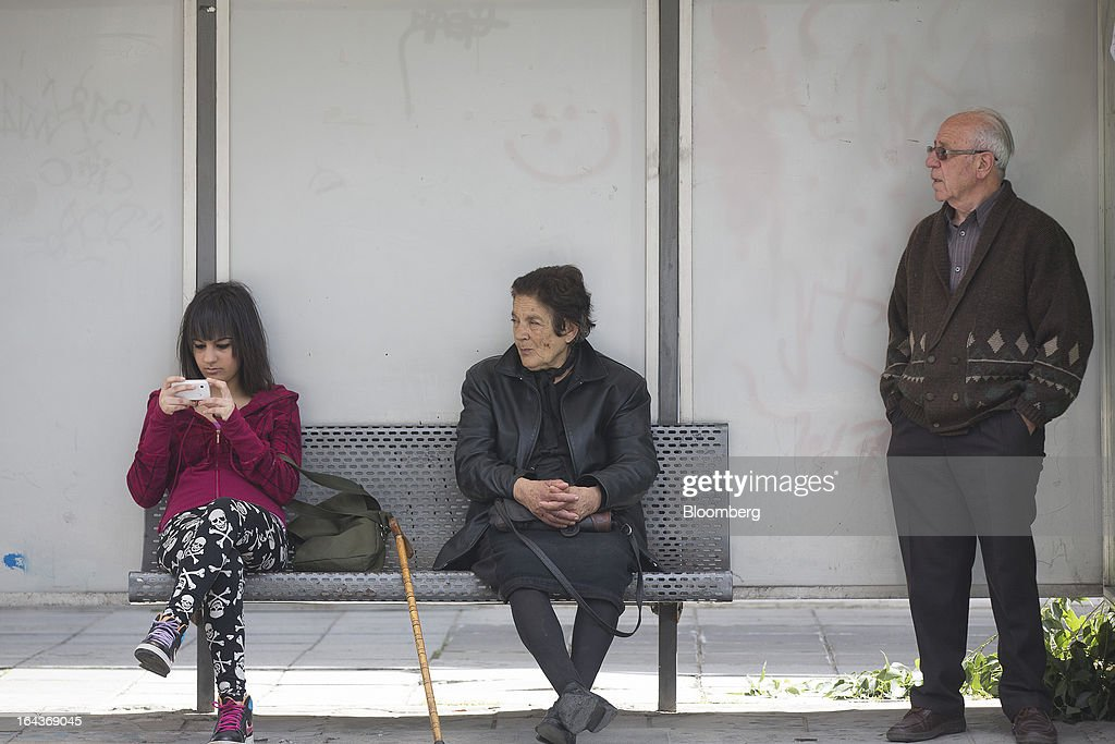 People sit and wait for a public bus at a roadside shelter in Nicosia, Cyprus, on Saturday, March 23, 2013. The aid package Cyprus is seeking would only provide temporary relief as it risks triggering a capital flight that would push the nation closer to needing to restructure its debts. Photographer: Simon Dawson/Bloomberg via Getty Images