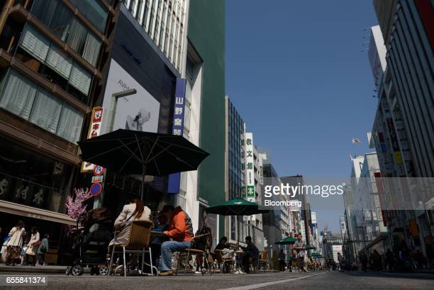 People sit and walk along a road temporarily made carfree in the Ginza district of Tokyo Japan on Monday March 20 2017 Japan's land prices will be...