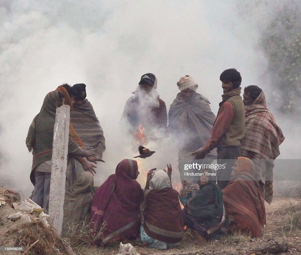 People sit around a bonfire to keep themselves warm on a cold in dense fog at Mayur Vihar, as temperature dips below 6 degree Celsius on January 2, 2013 in New Delhi, India. There was no respite from cold and dense fog in North India as mercury dipped two degrees below normal to stay at 4.8 degree Celsius.