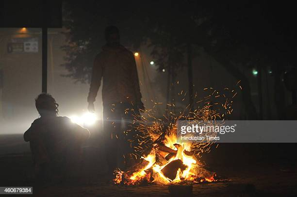 People sit around a small bonfire during a cold and foggy morning on December 18 2014 in Noida India Fog and mist continued to affect normal life and...