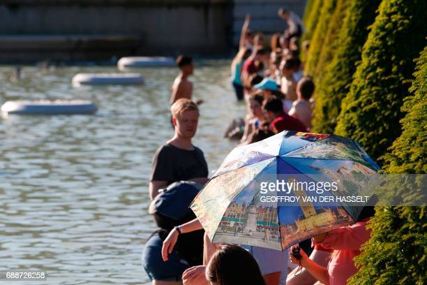 People sit around the Fountain of Warsaw at the Gardens of the Trocadero and enjoy the sun during warm temperatures in Paris on May 26 2017 / AFP...