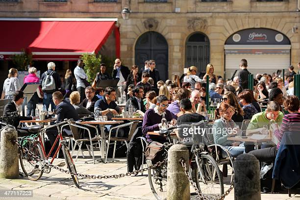 People sit at a cafe terrace on a sunny day in Bordeaux southwestern France on March 7 2014 AFP PHOTO / NICOLAS TUCAT