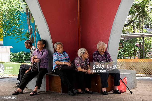 People sit at a park in the Shau Kei Wan district of Hong Kong China on Friday June 19 2015 Hong Kong is scheduled to release consumer price index...