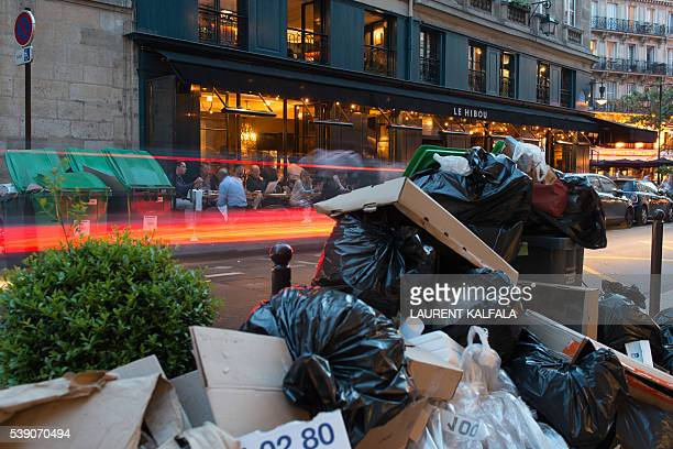 People sit at a restaurant terrace while rubbish bins and bags wait to be collected on the other side of the street in the SaintGermaindesPres...