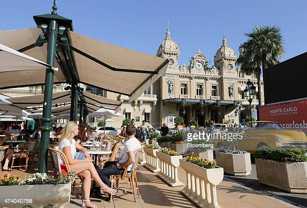 People sit at an outdoor cafe terrace as the Casino de MonteCarlo stands beyond in Monaco on Monday May 18 2015 The ultraluxury housing market is...