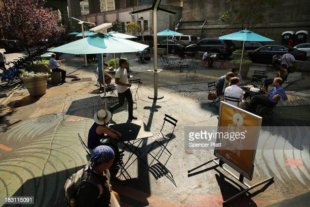 People sit at an outside cafe in Dumbo on October 4 2013 in the Brooklyn borough of New York City A group of five prominent properties in Dumbo owned...