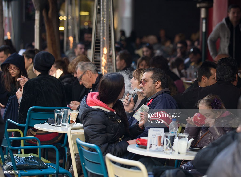 People sit at outside tables in a cafe following the electoral success by Syriza in the Greek general election yesterday on January 26 2015 in Athens...