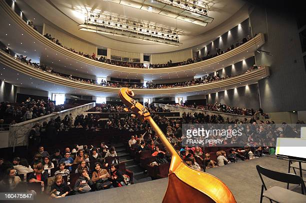 People sit at the Baudelaire public studio as a double bass is pictured in the foreground during the 'Folle Journee' classic music festival on...