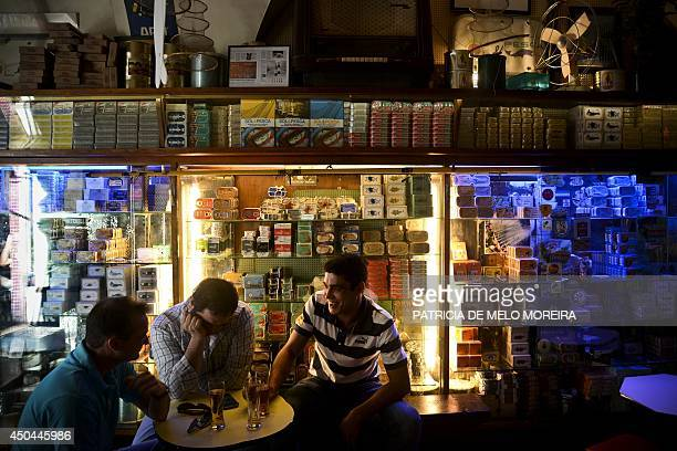 People sit at the traditional canned fish bar 'Sol e Pesca' at Cais do Sodre in Lisbon on June 10 2014 The bar used to be an old fishing shop named...
