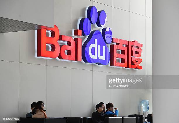 People sit below a Baidu logo at the Baidu headquarters in Beijing on December 17 2014 Baidu China's leading search engine and ride sharing company...
