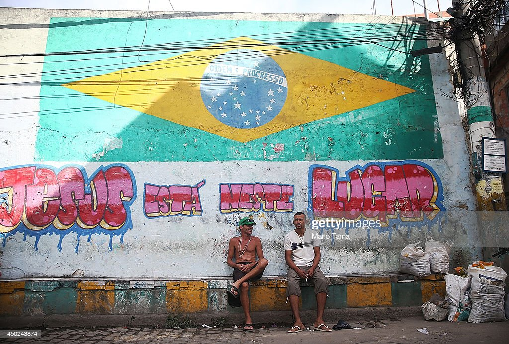 People sit beneath a Brazil flag painted in the occupied Complexo da Mare, one of the city's largest 'favela' complexes, on June 7, 2014 in Rio de Janeiro, Brazil. The Brazilian government has deployed nearly 3,000 federal troops to occupy the group of violence-plagued slums ahead of the 2014 FIFA World Cup. The group of 16 communities house around 130,000 residents and had been dominated by drug gangs and militias. Brazil is in final preparations to host the World Cup which kicks off June 12.