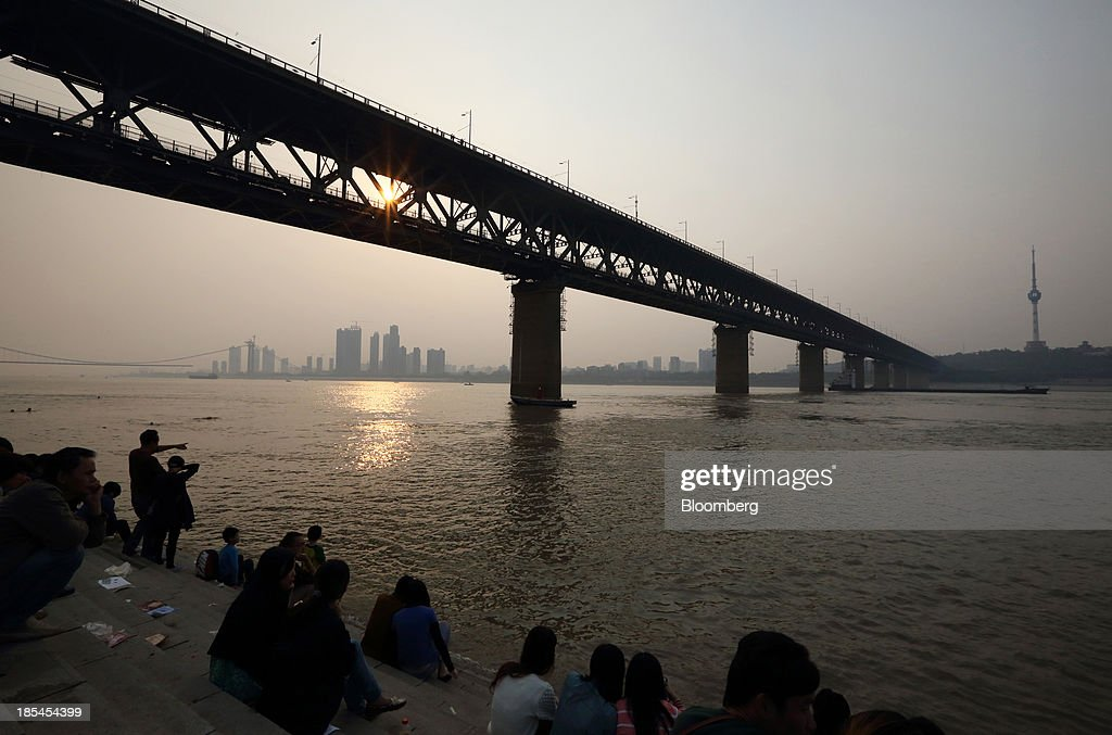 People sit beside the Chang Jiang river at dusk in Wuhan, China, on Sunday, Oct. 20, 2013. China's economic expansion accelerated to 7.8 percent in the third quarter from a year earlier, the statistics bureau said Oct. 18, reversing a slowdown that put the government at risk of missing its 7.5 percent growth target for 2013. Photographer: Tomohiro Ohsumi/Bloomberg via Getty Images