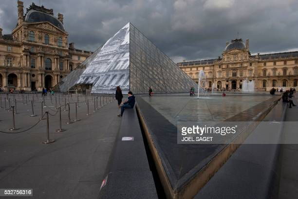 People sit by a fountain in front of the Louvre Pyramid covered with a giant photograph of the museum by French artist and photographer JR on May 19...