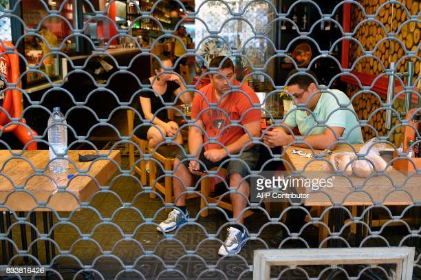 People sit in a bar behind an iron curtain as they wait after a van ploughed into the crowd killing 13 persons and injuring over 50 on the Rambla in...