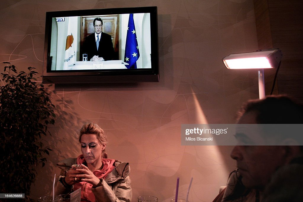 People sit in a bar while the President of Cyprus, Nicos Anastasiades, make a statement on television on March 25, 2013 in Nicosia, Cyprus. After days of negotiation, Eurozone finance ministers have agreed terms for a 10 billion euro bailout deal, which aims to prevent the collapse of Cypriot banks and ensure that Cyprus remain in the Eurozone. The agreement, which has been described by Cyprian politicians as 'painful', will see large bank account holders suffer big losses.