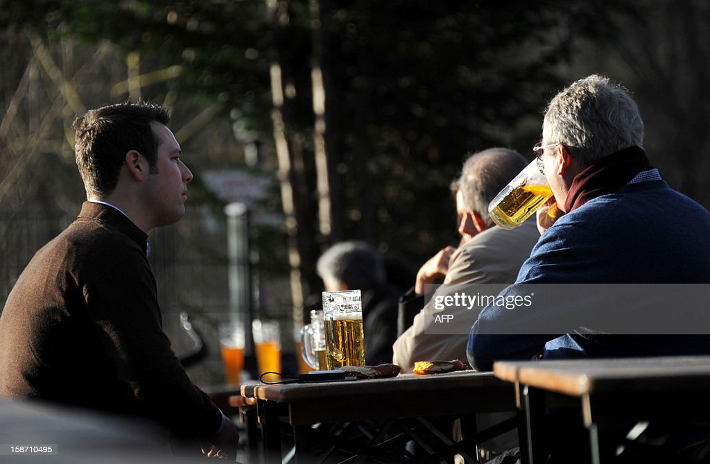 People sit in a beer garden at the English Gardens in Munich, southern Germany where temperatures reached 20 degrees Celsius on December 25, 2012 breaking all records for this time of the year. AFP PHOTO / TOBIAS HASE GERMANY OUT