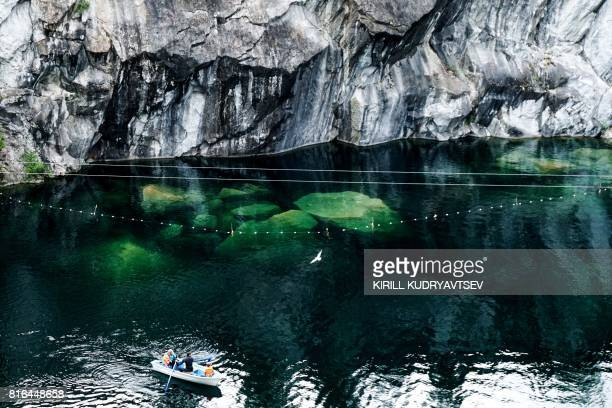 People sit in a boat floating in a marble quarry close to village of Ruskeala republic of Karelia on July 17 2017 / AFP PHOTO / Kirill KUDRYAVTSEV