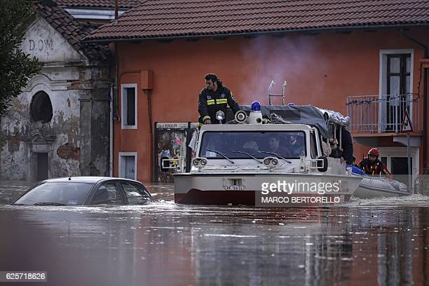 People sit in a boat of the Italian fire fighters as they help them to evacuate from their home in Moncalieri near Turin on November 25 2016 because...